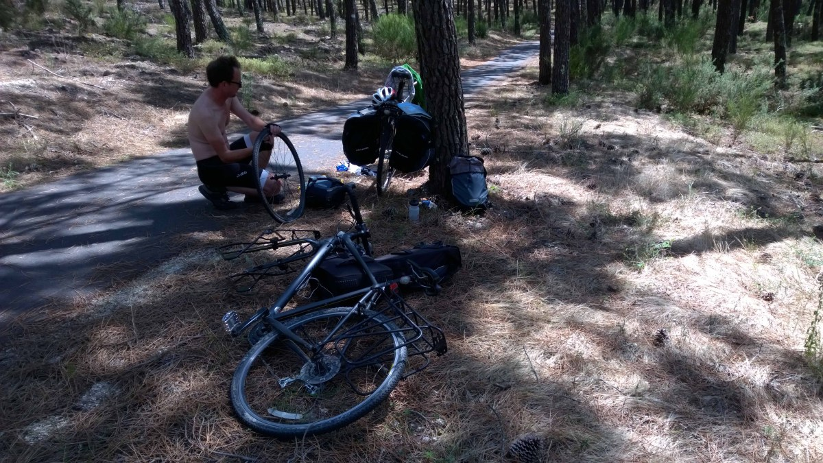 Photograph of Keith fixing a puncture in a shaded forest in France.