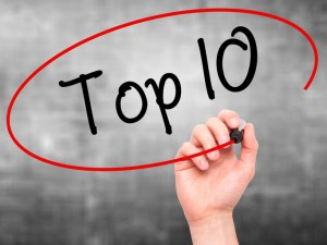 Hand writing Top 10 with marker on visual screen.