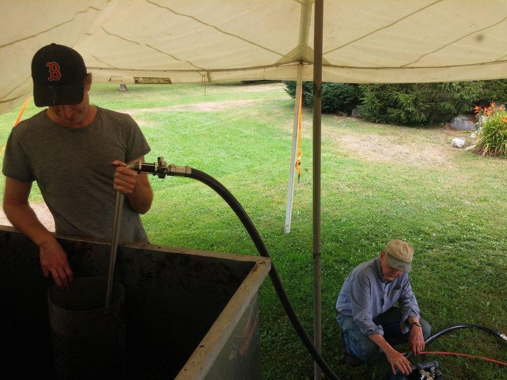 Eric draining a fermenter after fermentation with David tending the pump