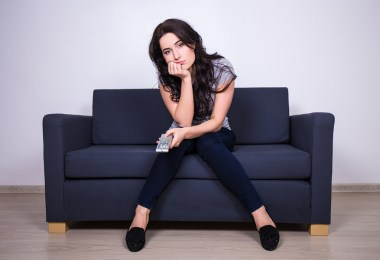 Woman Sitting On Sofa And Watching Tv