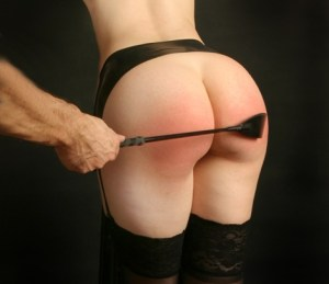 man spanking with crop on bare bottom of woman wearing suspenders