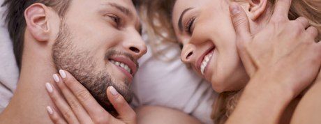 Man and woman in bed laughing together