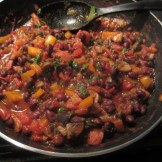 Cooked beans, peppers, onions, sausage, and diced tomatoes