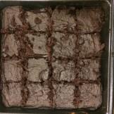 Baked brownies in baking pan, sliced
