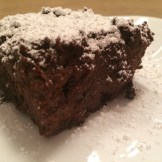 Side view of a single brownie covered in powdered sugar on white plate