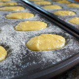 Buttered and floured madeleine pans filled with batter