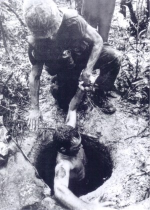 A comrade helps Bowman climb out of a Viet Cong tunnel.