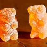 A marijuana-infused sour gummy bear candy is shown next to a regular one at right in a photo illustration in Golden