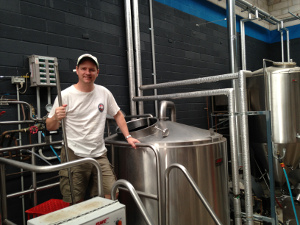 Wayward brewer Peter Phillip standing on a brewhouse