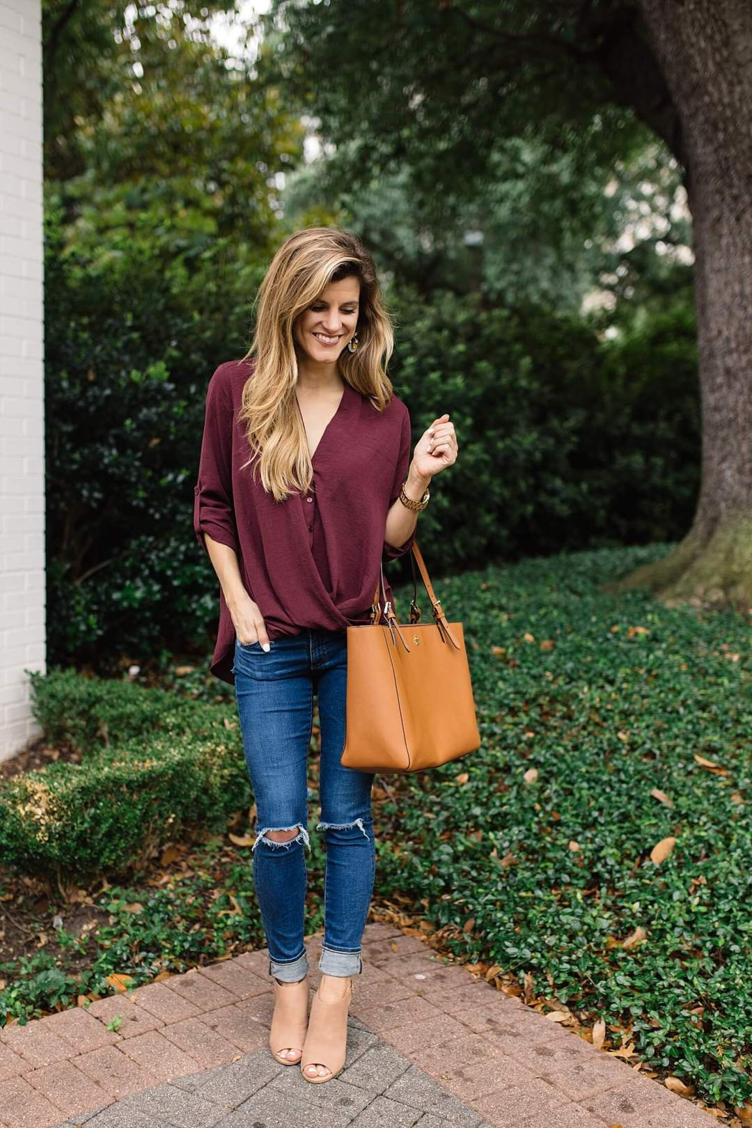 transitional summer to fall cute outfit idea with burgundy blouse, distressed denim and peep toe booties