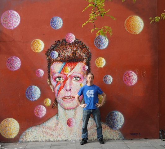 JimmyC with the portrait of David Bowie on the side of Morley's in Brixton