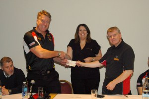 John Bastian receives cheque from BullBuilder