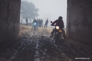 Bulleteers riding through a small under bridge crossing on their way to holipura