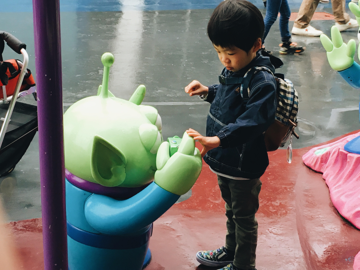 A young boy trying to high-five a Little Green Man!