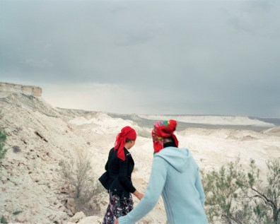 Two sisters run down to the underground mosque in Beket-Ata. They have come on a pilgrimage with their family from Aktau, to pray for the recovery of their uncle. Beket-Ata Necopolis, Kazakhstan.