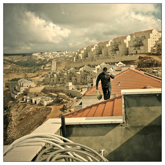 A Palestinian worker fixing the roof tops of the new construction. It is estimated that at the end of 2011 the population of the settelment would reach 50,000.