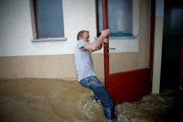 Wroclaw, Poland. A man struggles to open the door to his block of flats during the flood.