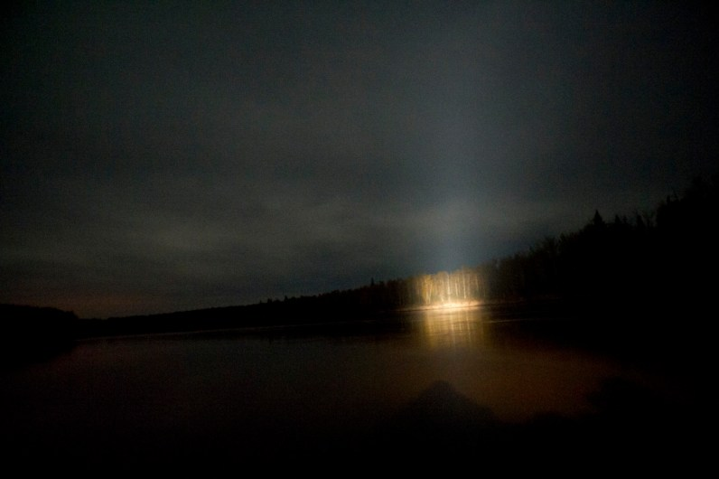 The shoreline of Athabasca River is illuminated by the spotlight of a barge. Contaminants such as arsenic, mercury and other heavy metals are flowing downstream to the isolated indigenous community of Fort Chipewyan from Canada's Oil Sands -- the largest industrial project on Earth.