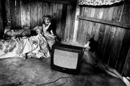 BRAZIL, SANTAREM. NOVEMBER 2008. Two children, one of them disabled (right), crying in their home after being abandoned by their mother who escaped after stabbing her partner. Most of the soya displaced families have to live in miserable conditions of poverty, violence and marginality in slums of the city of Santarem.