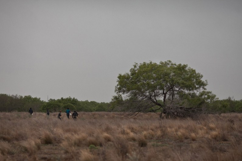A group of migrants runs into the brush after being spotted by the U.S. Border Patrol. (Dominic Bracco II/ Prime For The Washington Post)