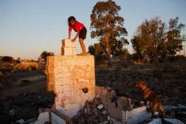 A young girl and her dog play on what remains of an old house in Wilcannia. The home was abandoned and left to crumble after a family member passed away. David Maurice Smith/Oculi.