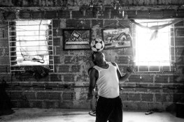 A kid play with a soccer ball inside his apartment in the 8th floor