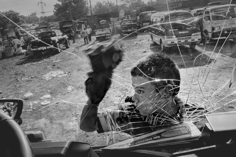 "Nicaragua, Managua, in tha market so named ""Mayoreo"". A boy cleaning the windshields of cars for few pesos per day. In Central America and especially in Nicaragua, although compulsory education is planned up to 12 years, according to World Bank estimates, around 10% of children under 18 years living and working on the street. According to recent studies, approximately 320,000 children and young people between 5 and 14 years of age are forced to work."