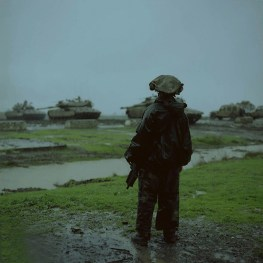 A combat soldier alone in the rain during an exercise.
