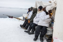 Captain Edward Itta communicates with other whalers as his crew waits at the edge of the cove Whalen, Jason and boat driver Price Itta cut out of the sikuliak. Utkeagvik.