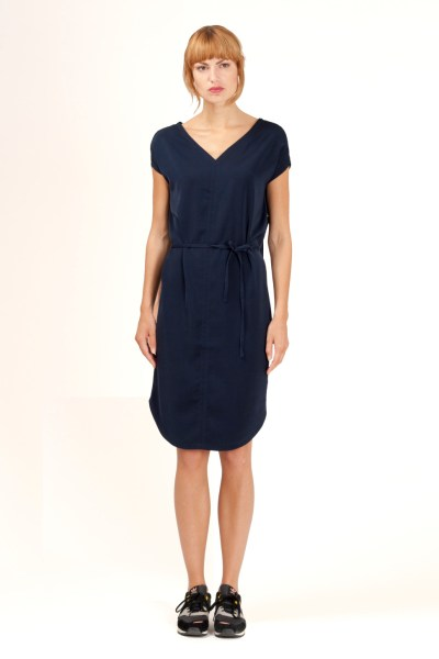 Sleeveless loose fit dress in night blue. Deep V-neck in front and an open back in night blue lace. The waist is pinned by a small fabric belt. By Barbara van der Zanden