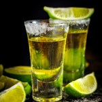 Mexican Gold Tequila with lime and salt on black table. Two Tequila shots. Alcohol drink.