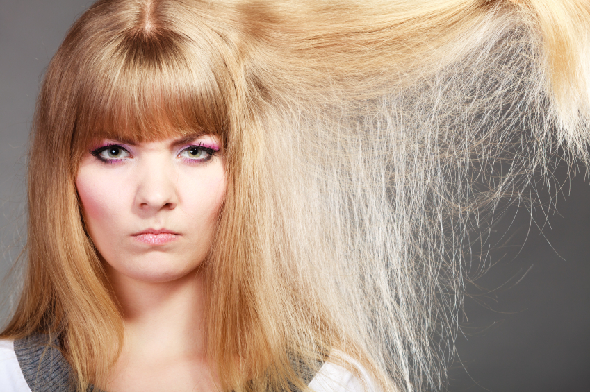 Haircare. Blonde woman with her damaged dry hair angry face expression gray background