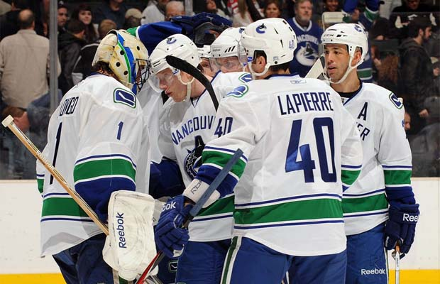 Roberto Luongo is congratulated by his Vancouver Canucks teammates for recording his 300th career win