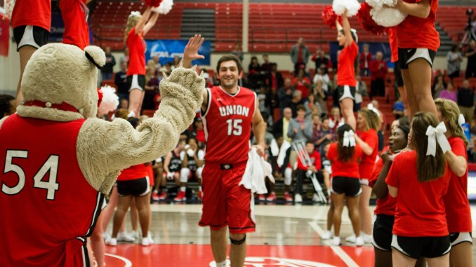 Felipe Rocha looks to give Buster a high five at Bulldog Madness.   Photo by Morgan Morfe, Staff Photographer