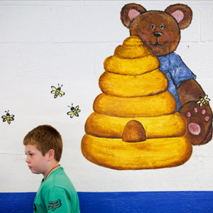 "Lucas Phillips, a third grader, walks past a bear and honey painting in the lunchroom at Bee Log Elementary, in Yancey County. The school's motto is ""If you believe it you can achieve it."" Matt Rose/Carolina Public Press"