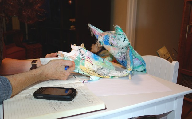 The Chairman, a cute cat doll, is vieweing hand painted fabric.