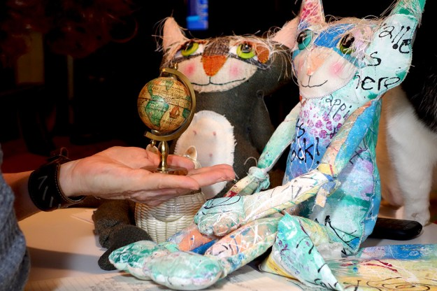 A small globe of the world is presented to two cute cat dolls.