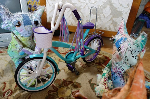 The Chairman and his fellow cat dolls gather around to look at a miniature bicycle.