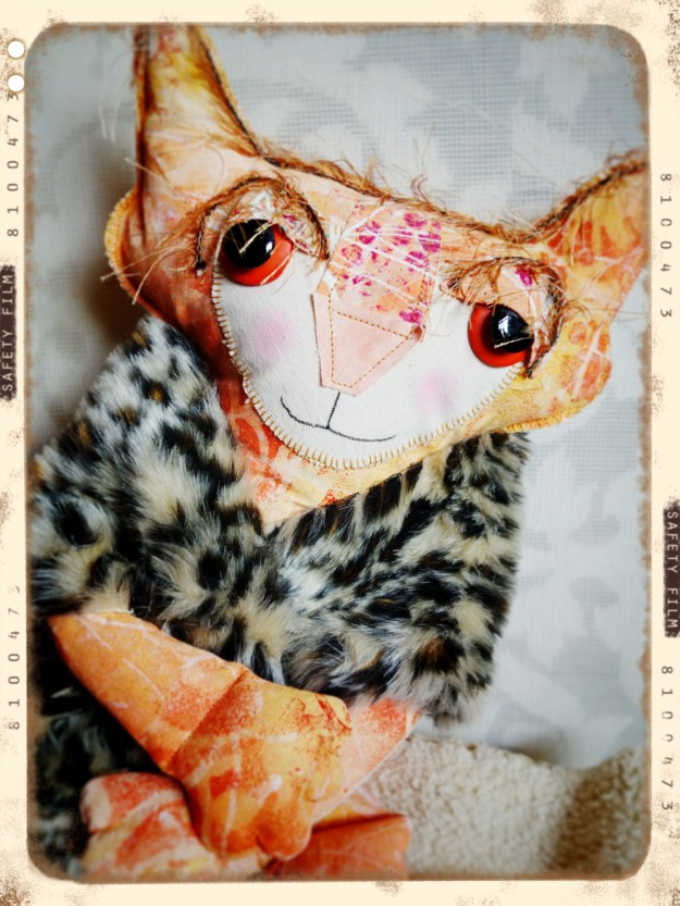 A sweet and full-throttle beauty shot of Ginger the soft scuptured cat doll wraped in and animal skin fluffy fabric.