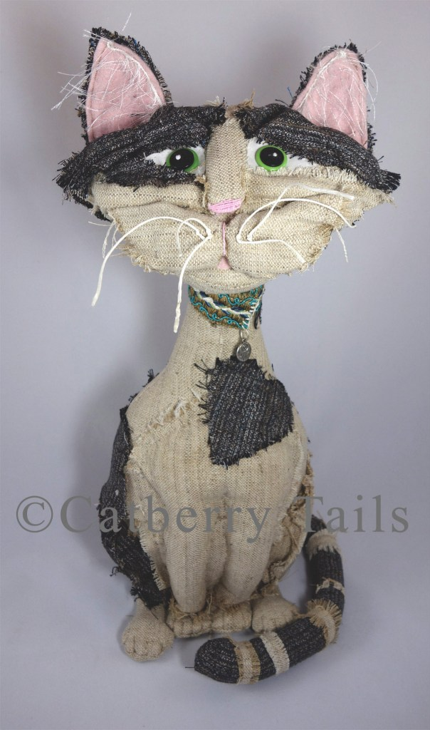Opie the Soft sculptured cat dall stands about 18 inches tall and is made out of recycled mens' suits.