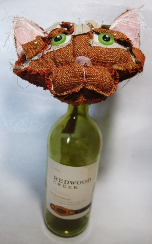 Orange soft-sculptured cat doll head propped on top of an empty large wine bottle. Pins are holding fabric in place.