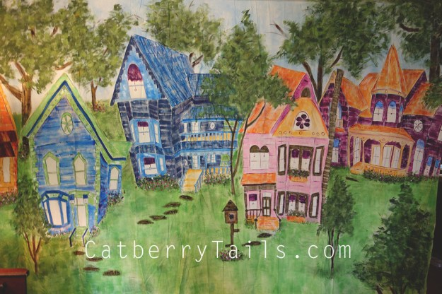 Colorful, huge hand painted canvas of whimsical houses surrounded by trees and grass and birdhouses.