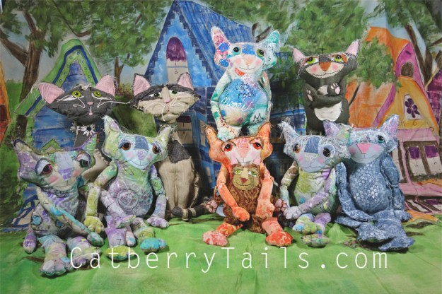 All the whimsical cat dolls are gathered for an official portrait in front of a giant hand painted mural.