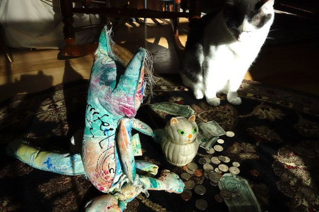 The Chairman cat doll sitting with coins, dollar bills and his curse jar.