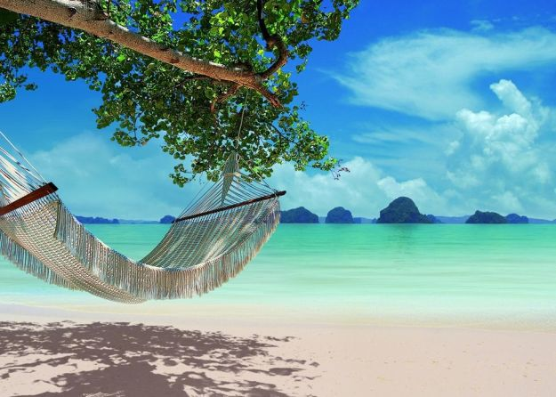 An idyllic hammock on a white sand beach of Krabi Thailand.