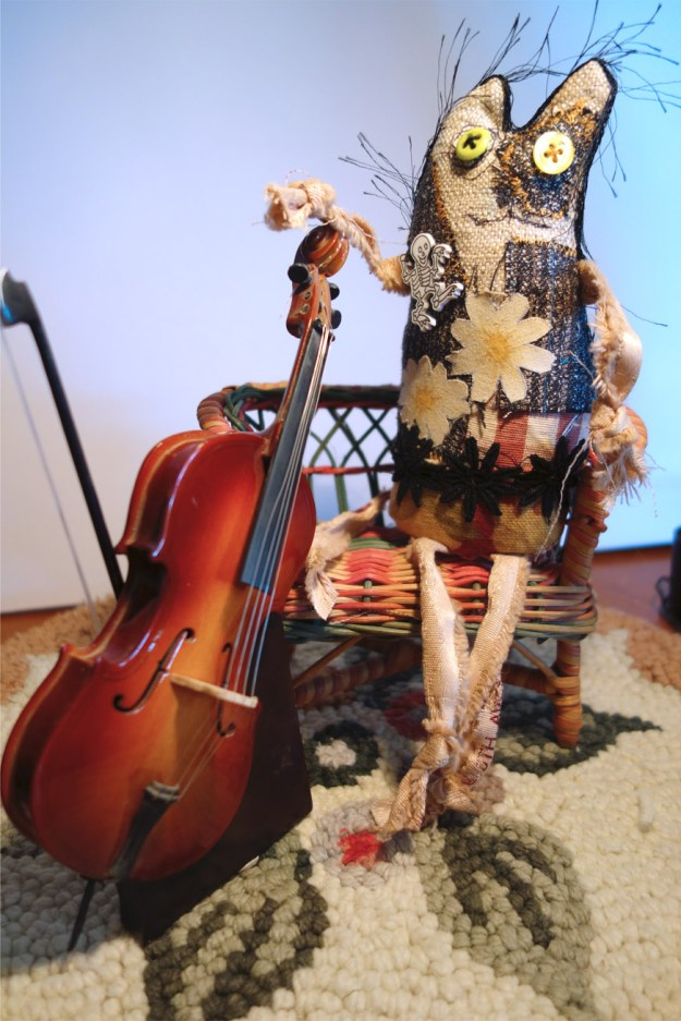 Frankencat poses with his cello as it rests on the cello stand. Very professional musician type photo.