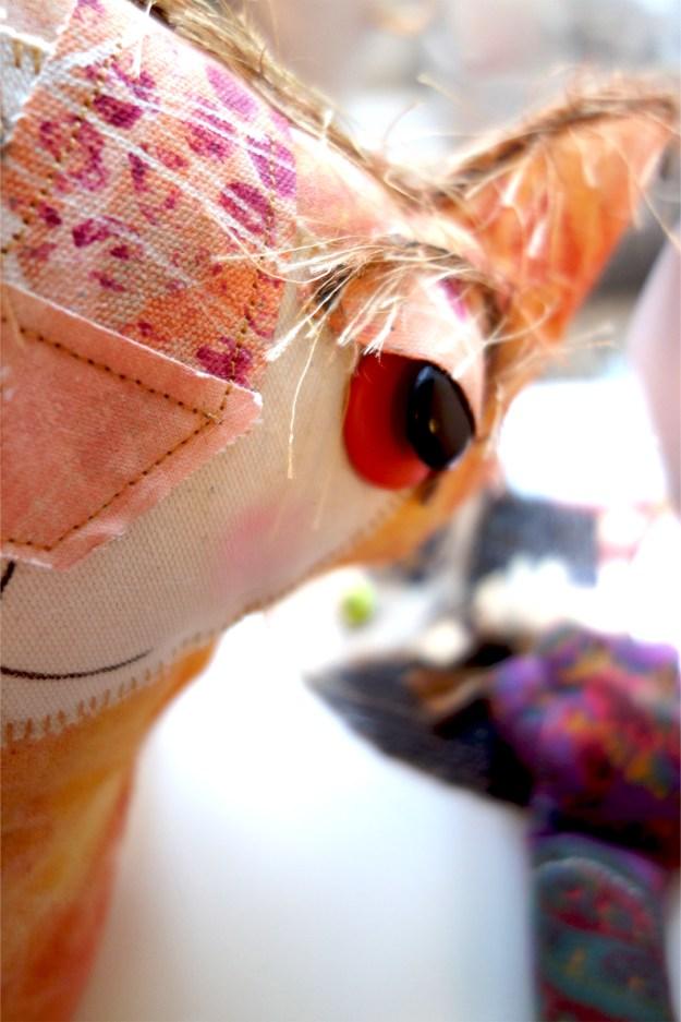 Ginger, the orange floppy cat doll takes a selfie.