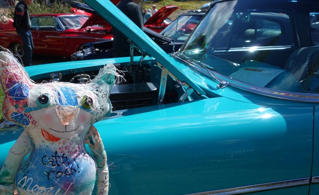 A turquoise vintage car, spit polished and gleaming. The Chairman poses next to it.