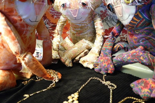 Three adorable soft sculpture cat dolls are huddled around the jewelry. Ginger is holding one across her paw.