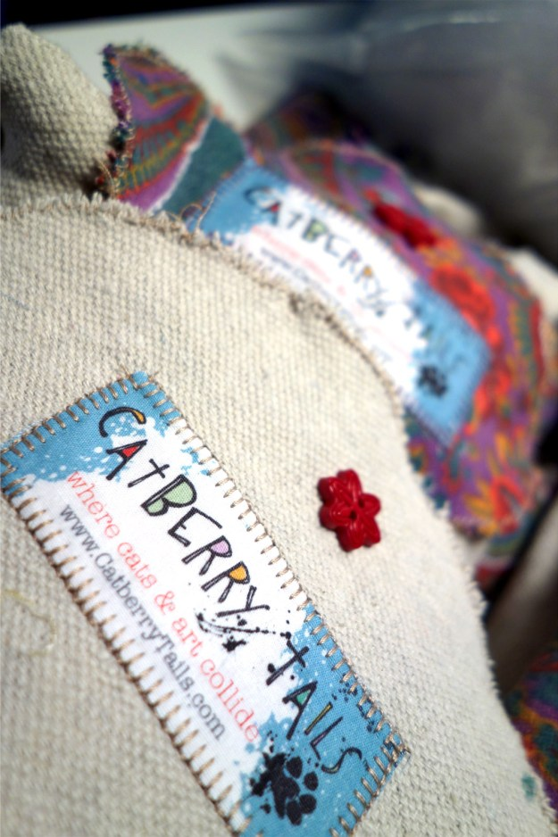 A photo of the Catberry Tails label sewn onto fabric and a button flower above it.